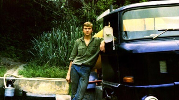 Junger Mann steht neben einem kleinen Lastwagen