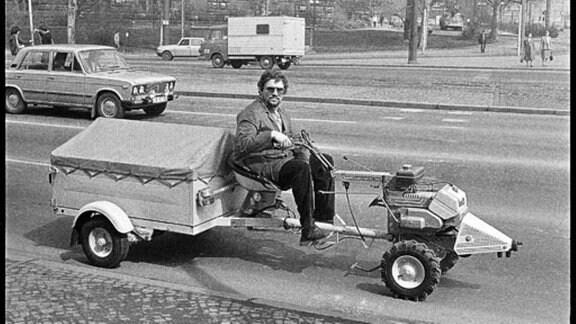 Ein Mann auf einem Anhänger mit Motor vorne dran.