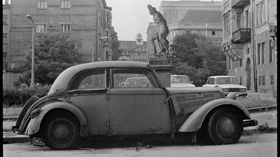 Ein völlig alter und kaputter Wartburg vor einer Statue.