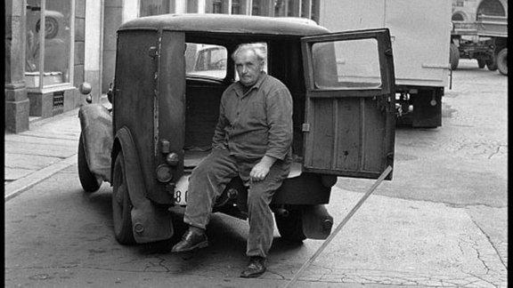 Älterer Mann sitzt in seinem Auto.