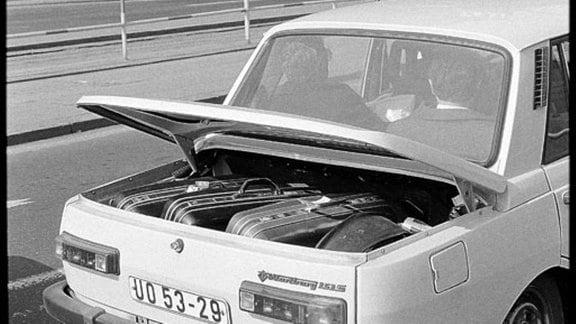Beim Taxi steht der Kofferraum offen, da zu viele Koffer darin sind.
