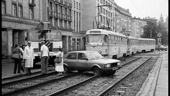 Auto steht auf Straßenbahnschienen, deswegen kann die Straßenbahn nicht weiter fahren.