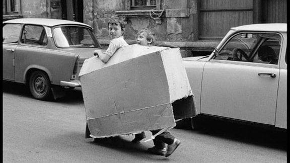 zwei kleine Jungs laufen auf der Straße mit einem Pappkarton herum und Spielen Auto.Dahinter stehen auch zwei Pappkartons, jedoch richtige Autos. Trabbis.