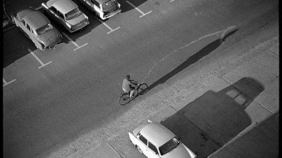 Parkende Autos, ein Radfahrer und lange Schatten.