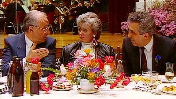 Egon Krenz und ein weiterer Mann mit einer Frau sitzen an einer festlich gedeckten Tafel