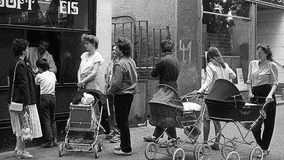 Frauen mit Kinderwagen stehen in einer Schlange vor einem Eisladen.