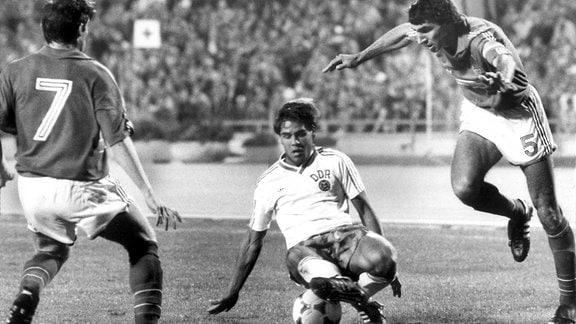 DDR-Stürmer Ulf Kirsten (mitte) kommt mit dem Ball vor den französischen Gegenspielern Alain Giresse (links) und Maxime Bossis zu Fall.