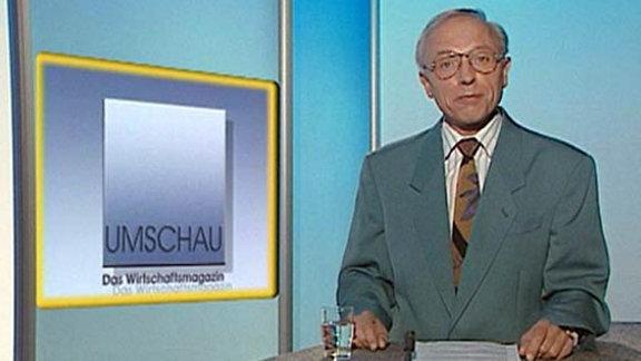 Manfred Vieweg vor gelbem Moderationspult mit Moderationszettel und Wasserglas
