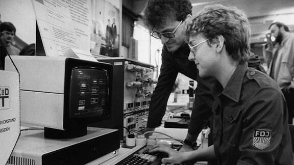 Jugendliche in FDJ-Kleidung an einem Computer auf der Messe der Meister von morgen (MMM) in Berlin (Ost), aufgenommen 1988.