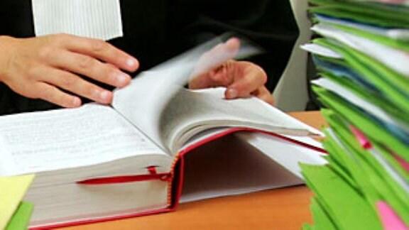 Ein Rechtsanwalt schlägt in Gesetzesbüchern nach colourbox953266