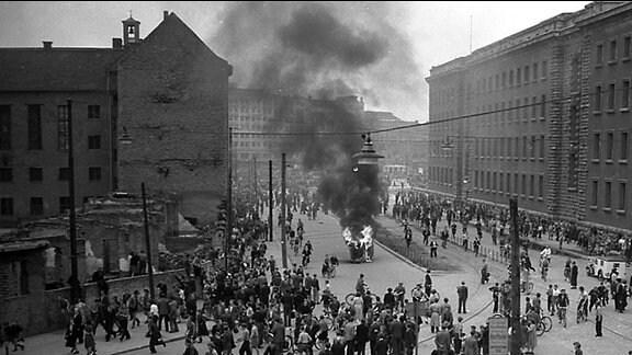 Berlin, 1953 : Eine gepanzerte Skoda-Limousine wurde als Funktionärsauto der SED erkannt umgestürzt und in Brand gesteckt. Im Hintergrund das Berolinahaus am Alexanderplatz.