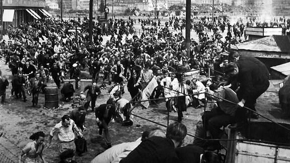 Berlin:Teilnehmer des Arbeiteraufstands in Ostberlin flüchten vor Panzern