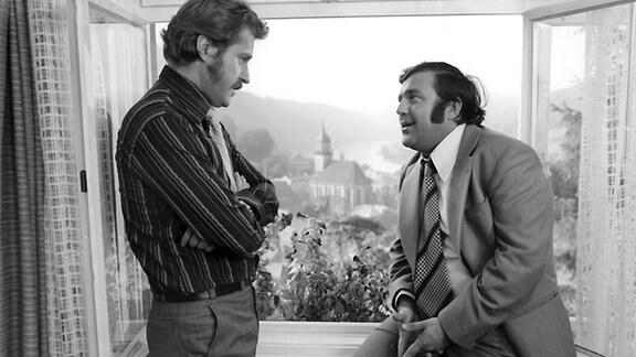 Schwarz-Weiß-Bild: Zwei Männer stehen vor einem geöffneten Fenster und unterhalten sich.
