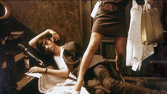 Eine Frau steigt über einen Mann, der vor ihrer Wohnungstür liegt.