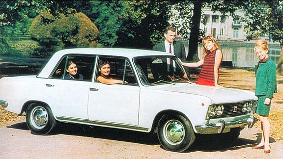 Aus einem weißen Auto gucken junge Menschen heraus, dahinter ein Teich mit Bäumen