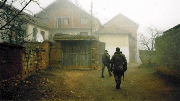 Zwei Soldaten gehen an aufgeschlichtetem Holz auf ein Haus zu