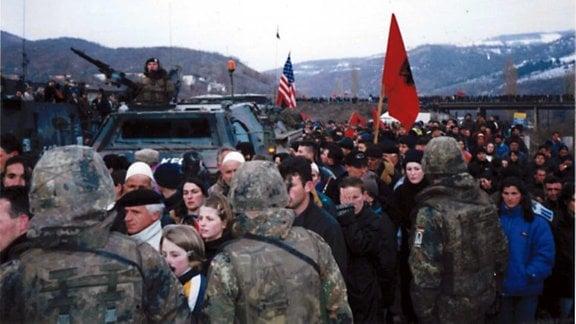 Mengeschenmenge um ein Militärfahrzeug geschart, aus dessen Dachluke ein Soldat mit Maschinengewehr rausguckt