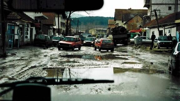 Blick aus einem Auto auf eine schlammige Straßen zwischen einer Häuserreihe