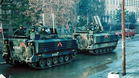 Auf einer Straße fahren zwei Panzer aus denen Soldaten herausgucken