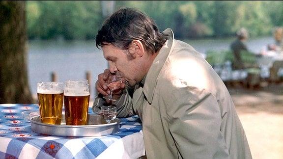Ein Mann an einem Tisch mit karierter Decke, vor ihm stehen mehrere volle Gläser mit Bier
