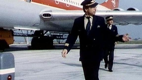DDR Piloten, im Hintergrund ein Flugzeug