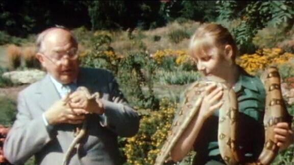 Heinrich Dathe zieht eine drei Monate alte Boa Constrictor aus seiner Jackentasche. Neben ihm steht eine Tierpflegerin mit einem ausgewachsenen Exemplar um den Hals.
