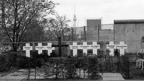 Berlin Mauerkreuze in der Nähe des Spreeufers am Reichstag erinnern an die Mauertoten. - Fahrradfahrer vor dem im Boden eingelassenen Mauererinnerungsstreifen.