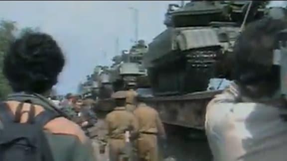 Mehrere Panzer stehen auf einem Zug.
