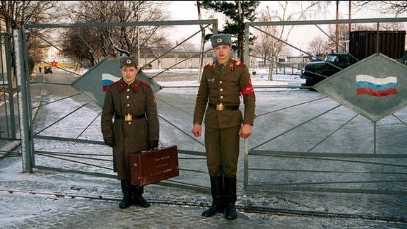 Russische Soldaten stehen vor einem Tor.