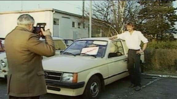 Ein junger Mann wird neben einem alten Opel Kadett fotografiert