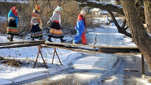 Eine Gruppe Mädchen, läuft gekleidet in Trachten, über die provisorische Brücke eines kleinen Baches