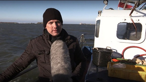 Ein Mann mit Mikrofon auf einem Fischkutter