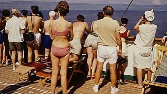 """Urlauber schauen vom Kreuzfahrtschiff """"Völkerfreundschaft"""" auf das Meer."""