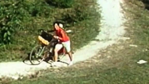 Kuba, eine Frau schiebt ein Fahrrad.
