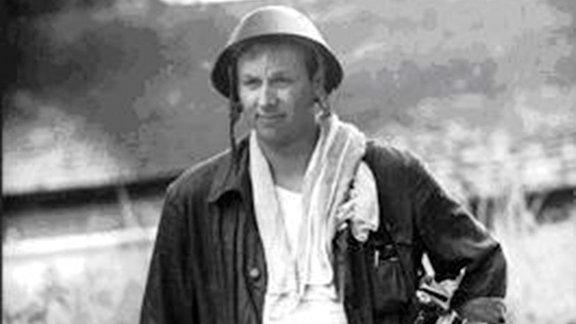 """Thomas Billhardt 1969 als Kriegs-Bildreporter in Hanoi, seine Kamera """"Pentacon Six"""" umgehängt und mit einem Stahlhelm auf dem Kopf."""