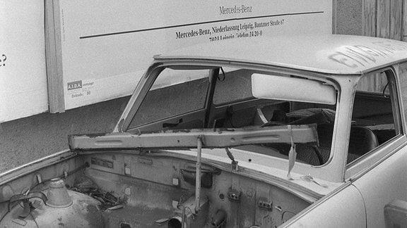 Ein abgewrackter Trabi parkt unter einem Mercedes-Werbeplakat mit dem Graffiti: Früher oder später... ein Pfeil weist auf das kaputte Auto.