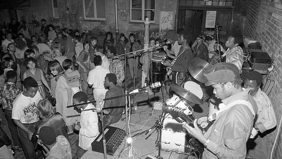 Eine Band spielt in einem Hinterhof.