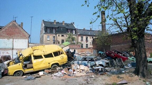 Hinter einer Mauer liegen wild durcheinander zahlreiche kaputte Autos