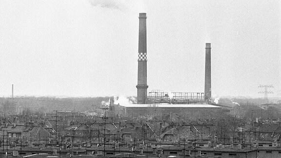 Blick über Häuser voller Antennen auf ein Kraftwerk mit qualmenden Türmen