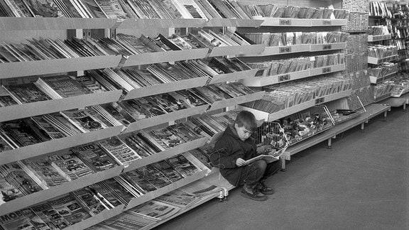 Ein kleiner Junge liest vor einem meterlangen Zeitungsregal in einem Magazin