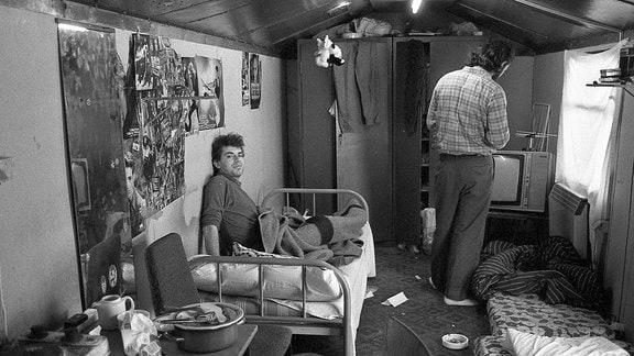 Blick in einen Wagencontainer: Eine Herdplatte, Plakate an den Wänden, ein Bett, zwei Männer, einer der Kamera abgewandt.