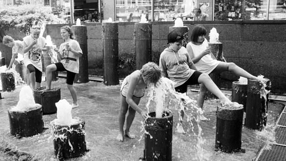 Kinder spielen an Wasserfontänen.