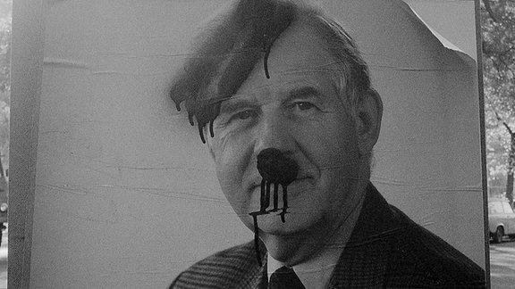 Ein Plakat mit Kurt Biedenkopf, dem mit Farbe ein Seitenscheitel und Oberlippenbärtchen Hitler ähnlich gemacht wurde. Die Farbe läuft aber aus.