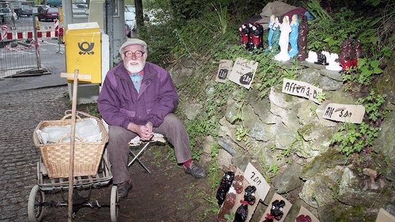 Ein bärtiger alter Mann verkauft Keramikfiguren zum  Stückpreis von fünf bis sieben Mark