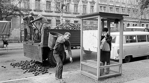 Eine Frau in einer Telefonzelle hält sich ein Ohr zu, weil draußen Kohlen von einem Laster geschaufelt werden.