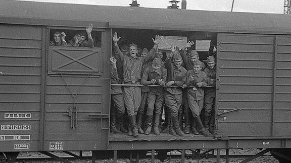 Russische Soldaten gucken aus einer offenen Waggontür