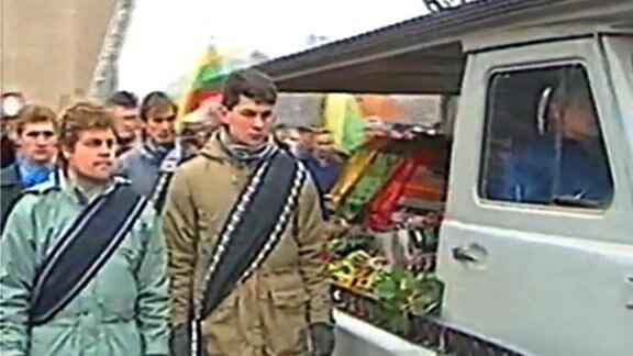 Menschen im Trauerzug begleiten einen Sarg