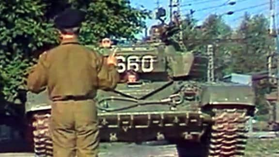 Soldat steht vor Panzer