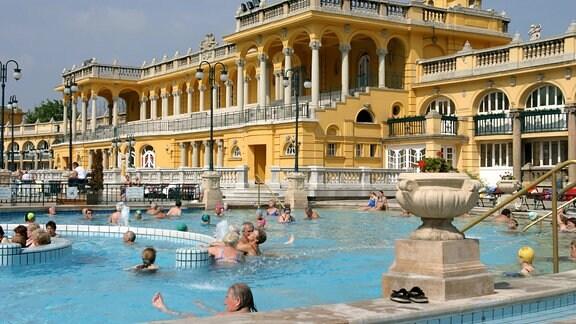 Heilbad Széchenyi in Budapest. Ein großes gelbes Gebäude, davor ein Wasserbecken mit vielen Menschen.