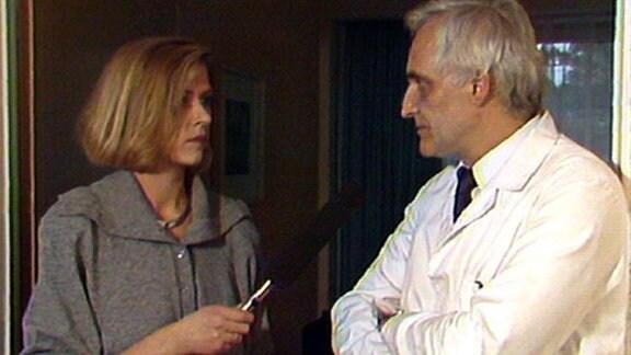 Frau mit Mikrifon und Mann im Arztkittel